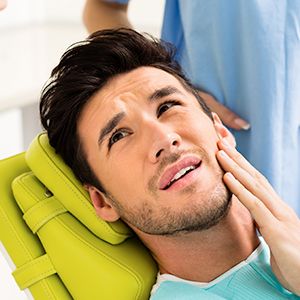 man in dental chair experiencing tooth pain