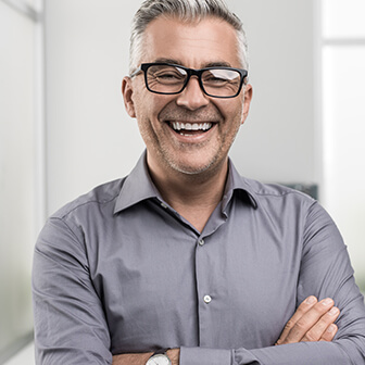 a man with glasses in a gray button down shirt smiling with partial dentures