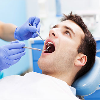 man having his teeth examined by a dentist