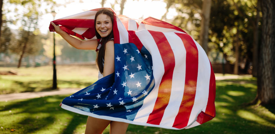 Brunette teenage girl smiles holding an American flag outside during the summer after her wisdom teeth removal