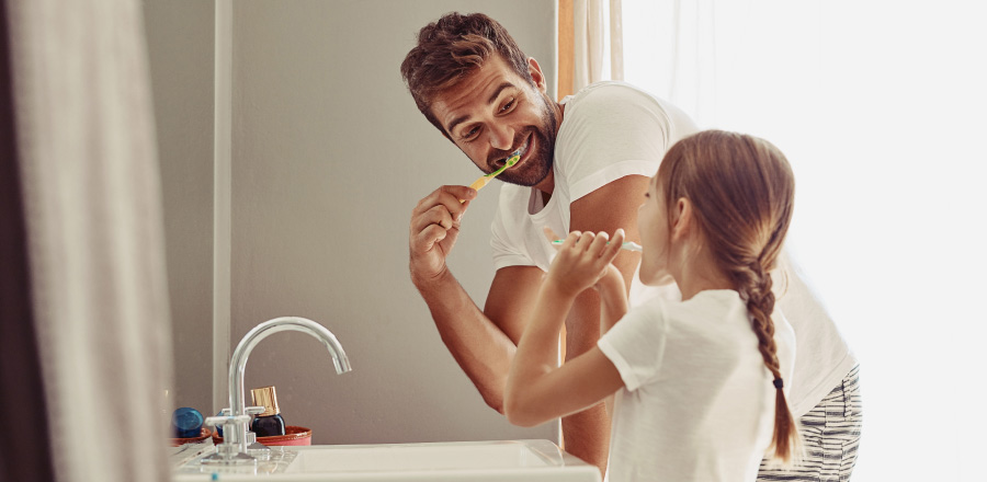 Dad & young daughter in white T-shirts leaning over the sink brushing their teeth together