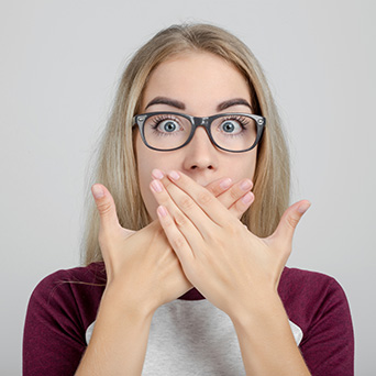 Nervous woman covering her mouth