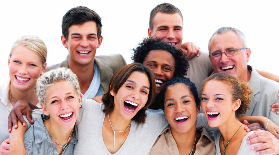 A group of 9 smiling friends of various ages, genders and ethnicities